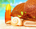 Beach items still life on on sandy coast straw hat with towel and sunscreen luxury spa resort summer vacation and travel Royalty Free Stock Images