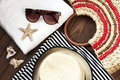 Beach items with straw hat,towel and sunglasses  on wooden background Royalty Free Stock Photo