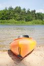 Beach kayak near woods on lake vertical format Stock Photo