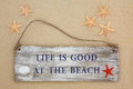 Beach life is good at the sign with starfish and cockle shell on sand background Stock Photography