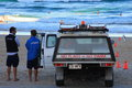 Beach lifeguards and vehicle standing beside their shortly before they close the gold coast australia Stock Photo
