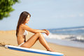 Beach lifestyle people woman enjoying summer sun and blue sky sitting relaxing with surfboard after bodyboarding in water Stock Image