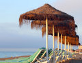 Beach lounge chair and beach umbrella at lonely sandy beach Royalty Free Stock Photo