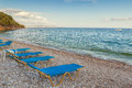 Beach lounge chairs in the evening at the shore of ionian sea empty golden hour near ipsos corfu greece Stock Image
