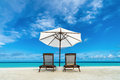 Beach lounger and umbrella on sand beach. Concept for rest, relaxation, holidays, spa, resort. Royalty Free Stock Photo