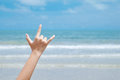Beach love hand sign over blue sea and sky background, summer tr Royalty Free Stock Photo