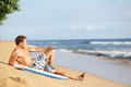 Beach man relaxing after surfing on beautiful handsome fit male model in swimming wear enjoying summer holidays vacation on Stock Photo
