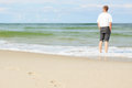 Beach man standing water back view shallow dof footprints sand Royalty Free Stock Photos