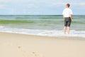 Beach man standing water back view shallow dof footprints sand Royalty Free Stock Photos