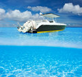 Beach and motor boat beautiful with white sand bottom underwater above water split view Royalty Free Stock Photo