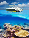 Beach and motor boat with coral reef underwater view beautiful bottom above water split Stock Photos