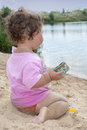 On the beach near the lake in the sand little girl playing with Royalty Free Stock Photo