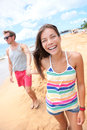 Beach people young couple holding hands walking interracial happy playful on having fun on travel vacation women smiling Royalty Free Stock Images