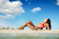 Beach pretty woman lying on sea on sky background Royalty Free Stock Image