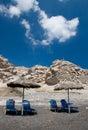 The beach with pumice rocks santorini greece sunbeds and umbrellas at Stock Photo