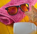 Beach resort concept. Female beach accessories on a blue yellow wooden background. Shell, glasses, towel, sunblock Royalty Free Stock Photo