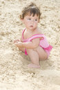 On the beach in the sand little girl sits and plays summer Stock Photography