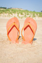 Beach sandals in sand orange flip flops front of dunes Stock Photo