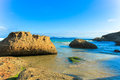 Beach scape with rocks in foreground and blue water and sky australian Royalty Free Stock Images