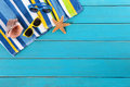 Beach scene with blue decking striped towel sunglasses starfish and seashell on old weathered painted wood space for copy Stock Images