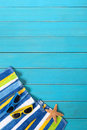 Beach scene with blue decking striped towel sunglasses starfish and seashell on old weathered painted wood space for copy Royalty Free Stock Photo