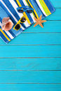 Beach scene with blue decking striped towel sunglasses starfish and seashell on old weathered painted wood space for copy Royalty Free Stock Photos