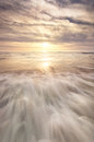 Beach scene showing water and sky and the sun shining Royalty Free Stock Photo