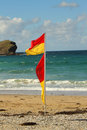 Beach scene summer with safety flag and rock Stock Photography