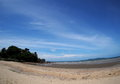 Beach sea scene view with deep blue sky and brown beach sand and stones Royalty Free Stock Photo