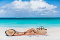 Beach sexy woman tanning with hat protecting face sunbathing lying down sleeping on white sand covering her straw for uv sun rays Royalty Free Stock Photo