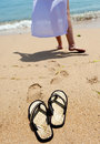 Beach slippers on sand, and female feet at a sea edge Royalty Free Stock Photos
