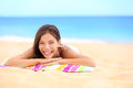 Beach summer woman sunbathing enjoying sun smiling lying down on towel looking away beautiful pretty cute multiracial asian Stock Image