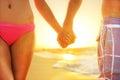 Beach sunset couple in love holding hands romantic on honeymoon bikini girl and casual beachwear men newlyweds people standing on Royalty Free Stock Photos