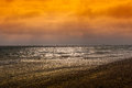 Beach sunset this is a picture of a summer at the british coast the sky is cloudy red there are waves coming to the shingle as Royalty Free Stock Photos
