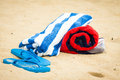 Beach towel and sandals on beach Stock Images