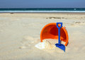Beach toys orange bucket blue spade and seashell on sunny sandy background Stock Photos