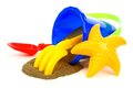 Beach toys with sand spilling toy pail rake shovel and starfish over a white background Royalty Free Stock Images