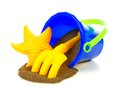 Beach toys and sand toy pail with spilling over a white background Royalty Free Stock Photo