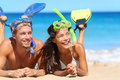 Beach travel couple having fun snorkeling happy young multiracial lying on summer sand with snorkel equipment looking Royalty Free Stock Images