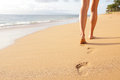 Beach travel woman walking on sand beach closeup leaving footprints in the detail of female feet and golden kaanapali Royalty Free Stock Images