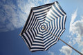 Beach umbrella on blue cloudy sky background and white Stock Photo