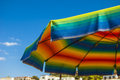 Beach umbrella colored like a rainbow expressing the idea of summer Stock Photography