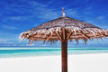 Beach umbrella on white sand next to lagoon Royalty Free Stock Images