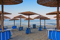 Beach umbrellas and chairs at dawn in greece Stock Images