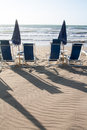 Beach umbrellas in front of the sea blue closed with seatings Royalty Free Stock Images