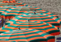 Beach umbrellas green and orange striped parasols Stock Image