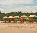 Beach umbrellas lounge chairs and colorful line the sandy in montanita ecuador south america on a sunny day Stock Photography