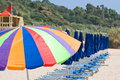 Beach umbrellas row of closed and large open colorful umbrella Stock Image