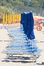 Beach umbrellas and sunbeds row of closed Royalty Free Stock Photo