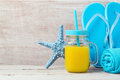 Beach vacation concept with orange juice and flip flops Royalty Free Stock Photo